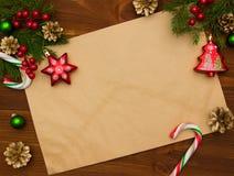 Tarjeta de felicitación en fondo de madera con las decoraciones de la Navidad Fotos de archivo