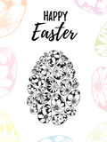 Tarjeta de felicitación feliz de Pascua con las letras dibujadas mano y huevos blancos y negros con los elementos florales Foto de archivo