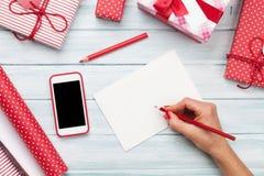 Tarjeta de felicitación femenina de la escritura y embalaje de los regalos de la Navidad Fotografía de archivo libre de regalías