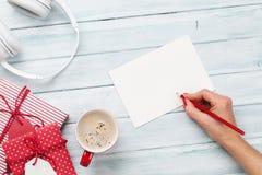 Tarjeta de felicitación femenina de la escritura y embalaje de los regalos de la Navidad Foto de archivo