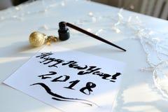 Tarjeta de felicitación festiva con el Año Nuevo hecho con tinta negra en el papel Imágenes de archivo libres de regalías