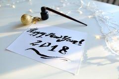Tarjeta de felicitación festiva con el Año Nuevo hecho con tinta negra en el papel Fotografía de archivo