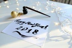 Tarjeta de felicitación festiva con el Año Nuevo hecho con tinta negra en el papel Imagenes de archivo