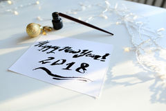 Tarjeta de felicitación festiva con el Año Nuevo hecho con tinta negra en el papel Imagen de archivo