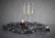 Tarjeta de felicitación hecha de la Navidad y bolas de la decoración del año del tejo, malla, candel y dos vidrios de champán con fotos de archivo