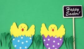 Tarjeta de felicitación hecha a mano de Pascua: pollo tramado en cáscara de huevo con la pizarra aislada en fondo verde Fotografía de archivo