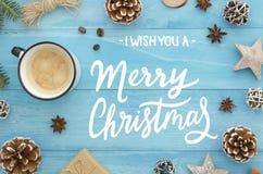 Tarjeta de felicitación de la Feliz Navidad con las letras en fondo de madera azul rústico con el café, caja de regalo, estrella  fotos de archivo libres de regalías