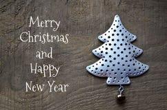 Tarjeta de felicitación de la Feliz Navidad y de la Feliz Año Nuevo Árbol de abeto decorativo en viejo fondo de madera Concepto d fotos de archivo libres de regalías