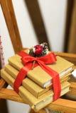Tarjeta de felicitación de la Navidad con la caja de regalo, el juguete del muñeco de nieve y las manoplas delante de la pared de imagenes de archivo
