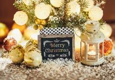 Tarjeta de felicitación de la Navidad con las chucherías, la linterna y el letrero Fotografía de archivo libre de regalías