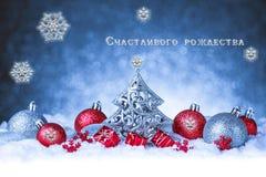 Tarjeta de felicitación de la Navidad con los copos de nieve y las bolas fotos de archivo