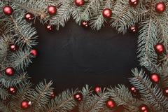 Tarjeta de felicitación de la Navidad en fondo negro Capítulo de las ramas del abeto adornadas con las bolas rojas fotografía de archivo libre de regalías