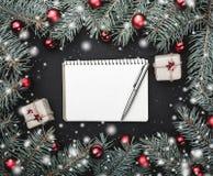 Tarjeta de felicitación de la Navidad en fondo negro Capítulo de las ramas del abeto adornadas con las bolas rojas Espacio para e imagen de archivo libre de regalías