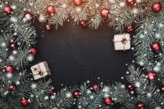Tarjeta de felicitación de la Navidad en fondo negro Capítulo de las ramas del abeto adornadas con las bolas rojas Regalos decora foto de archivo