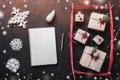 Tarjeta de felicitación de la Navidad, fondo negro, regalos hechos a mano en un rectángulo rojo Fotografía de archivo libre de regalías