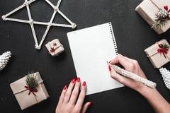Tarjeta de felicitación de la Navidad y Año Nuevo en fondo negro con los regalos modernos con una señora que escribe Imagen de archivo