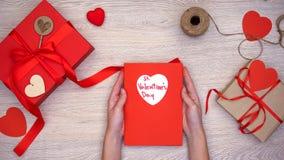Tarjeta de felicitación de la tenencia de la mujer con frase del St día de San Valentín, cajas de regalo en la tabla imágenes de archivo libres de regalías