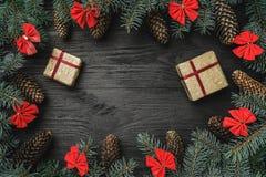 Tarjeta de felicitación de Navidad El abeto ramifica con los conos y los cuencos rojos, en fondo de madera negro Weihnachtspakete fotos de archivo libres de regalías