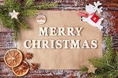 Tarjeta de felicitación por Año Nuevo con Feliz Navidad de la inscripción, alineada con las letras de madera del vintage Imagen de archivo