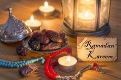 Tarjeta de felicitación que escribe a Ramadan Kareem con las fechas, rosario, velas fotografía de archivo libre de regalías