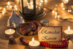 Tarjeta de felicitación Ramadan Kareem con las fechas, rosario, velas en tabla de madera marrón fotos de archivo libres de regalías