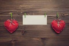 Tarjeta de felicitación vacía entre los corazones de Navidad Fotos de archivo libres de regalías