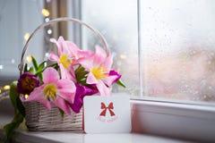 Tarjeta de felicitación y ramo blando de tulipanes rosados hermosos en la cesta blanca cerca de la ventana con las gotas de agua  Imágenes de archivo libres de regalías