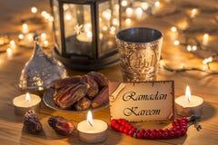 Tarjeta de felicitaci?n Ramadan Kareem con las fechas, el rosario, y la taza del agua del metal con el texto de Al? en ?rabe foto de archivo libre de regalías