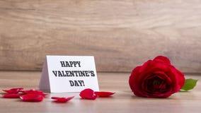Tarjeta de felicitación blanca con una muestra feliz del día de tarjetas del día de San Valentín al lado de un b Foto de archivo libre de regalías