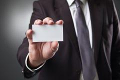 Tarjeta de la demostración del hombre de negocios en fondo gris oscuro Fotografía de archivo