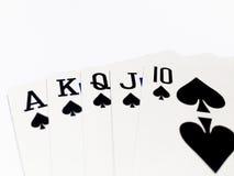 Tarjeta de la escalera real en juego de póker con el fondo blanco Imagen de archivo libre de regalías