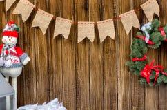 Tarjeta de la Feliz Año Nuevo con el muñeco de nieve y la guirnalda Fotografía de archivo