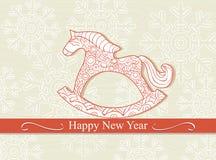 Tarjeta de la Feliz Año Nuevo con un caballo mecedora Imagen de archivo libre de regalías