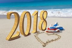 Tarjeta de la Feliz Año Nuevo Dos casquillos del ` s del Año Nuevo de Santa Claus en la playa y en corazón de la arena se dibujan Imagen de archivo libre de regalías