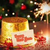 Tarjeta de la Feliz Año Nuevo que se inclina en el sombrero del partido del oro Foto de archivo
