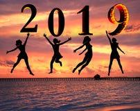 Tarjeta 2019 de la Feliz Año Nuevo Silueta de la mujer joven en la playa que salta como parte de la muestra del número 2019 con e fotografía de archivo libre de regalías
