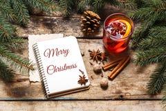Tarjeta de la Feliz Navidad con el vino reflexionado sobre en la madera Foto de archivo