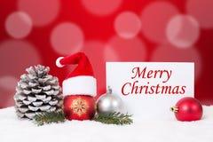 Tarjeta de la Feliz Navidad con la nieve, ornamentos, bolas, decoración del sombrero Imagen de archivo libre de regalías