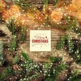 Tarjeta de la Feliz Navidad y del Año Nuevo en fondo de madera con las ramas del abeto, los conos del pino y los copos de nieve e libre illustration