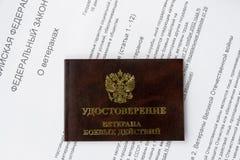 Tarjeta de la identificación del veterano en el fondo del texto de la ley federal de la Federación Rusa Fotos de archivo libres de regalías