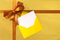 Tarjeta de la Navidad o de cumpleaños, arco de la cinta del regalo del oro, papel de embalaje llano del fondo del oro Fotos de archivo