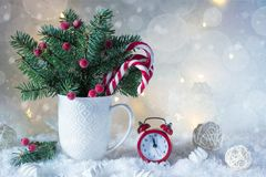 Tarjeta de la Navidad o del Año Nuevo Taza con los abetos, los bastones de caramelo y el reloj rojo Imagen de archivo