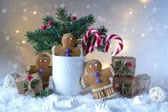 Tarjeta de la Navidad o del Año Nuevo Taza con los abetos, los bastones de caramelo y las galletas del jengibre Imagen de archivo
