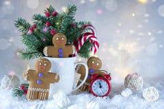 Tarjeta de la Navidad o del Año Nuevo Taza con los abetos, los bastones de caramelo y las galletas del jengibre Foto de archivo libre de regalías