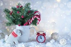 Tarjeta de la Navidad o del Año Nuevo Taza con los abetos, bastones de caramelo y reloj y galletas rojos en la forma de un perro Imagenes de archivo