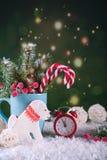 Tarjeta de la Navidad o del Año Nuevo Taza con los abetos, bastones de caramelo y reloj y galletas rojos en la forma de un perro Imágenes de archivo libres de regalías