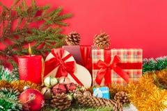 Tarjeta de la Navidad o del Año Nuevo Vela ardiente, conos, giftboxes, bolas con malla y rama de árbol de navidad en nieve contra Fotos de archivo