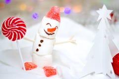 Tarjeta de la Navidad y del Año Nuevo con el muñeco de nieve de la melcocha y piruleta roja y un árbol de navidad blanco hecho de imágenes de archivo libres de regalías