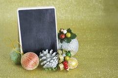 Tarjeta de la pizarra con el ornamento de la Navidad en fondo del oro Imágenes de archivo libres de regalías