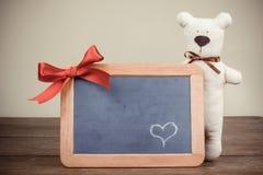 Tarjeta de la tarjeta del día de San Valentín con el oso de peluche, corazón en tarjeta negra de madera con el arqueamiento en est Imágenes de archivo libres de regalías